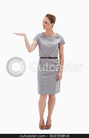 Woman in a dress presenting something with her hand stock photo, Woman in a dress presenting something with her hand against white background by Wavebreak Media