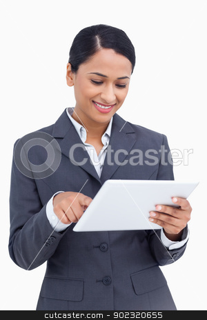 Close up of smiling saleswoman using her tablet computer stock photo, Close up of smiling saleswoman using her tablet computer against a white background by Wavebreak Media