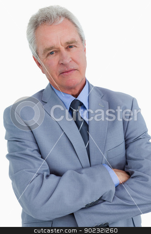 Close up of mature tradesman with his arms folded stock photo, Close up of mature tradesman with his arms folded against a white background by Wavebreak Media