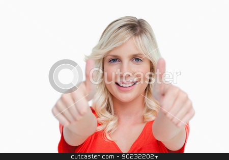 Attractive young woman showing her thumbs up in front of her stock photo, Attractive young woman showing her thumbs up against a white background by Wavebreak Media