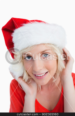 Young blonde woman putting on the Santa Claus hat stock photo, Young blonde woman putting on the Santa Claus hat against a white background by Wavebreak Media