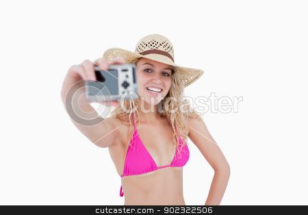 Beautiful teenage girl holding a camera while photographing hers stock photo, Beautiful teenager photographing herself with her camera against a white background by Wavebreak Media