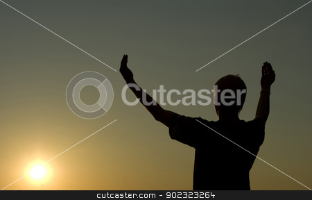 prayer stock photo, A man stands on against a sun with heaved up hands       by Vitaliy Pakhnyushchyy