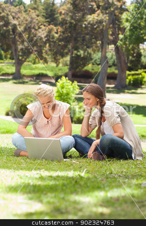 Smiling friends with a laptop sitting on the lawn stock photo, Smiling female friends with a laptop sitting on the lawn by Wavebreak Media