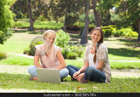 Smiling women sitting in the park with a laptop stock photo, Smiling young women sitting in the park with a laptop by Wavebreak Media