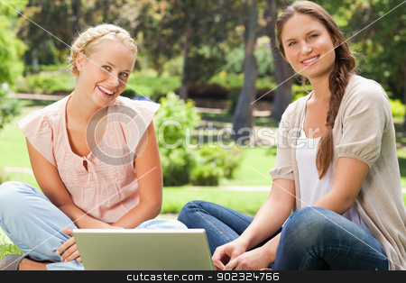 Smiling friends sitting in the park with a laptop stock photo, Smiling female friends sitting in the park with a laptop by Wavebreak Media