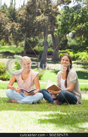 Smiling women with their books sitting in the park stock photo, Smiling young women with their books sitting in the park by Wavebreak Media