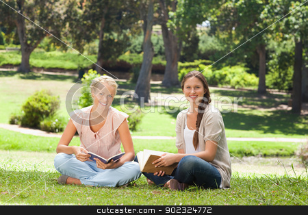 Friends sitting with their books in the park stock photo, Female friends sitting with their books in the park by Wavebreak Media