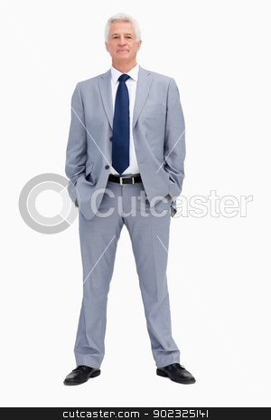 Portrait of a businessman with his hands in his pockets stock photo, Portrait of a businessman with his hands in his pockets against white background by Wavebreak Media
