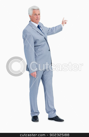 Portrait of a businessman pointing in his back stock photo, Portrait of a businessman pointing in his back against white background by Wavebreak Media