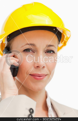 Portrait of a businesswoman on the phone wearing safety helmet stock photo, Portrait of a businesswoman on the phone wearing safety helmet against white background by Wavebreak Media