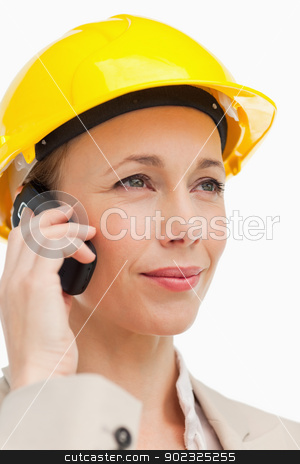 Woman on the phone wearing safety helmet stock photo, Woman on the phone wearing safety helmet against white background by Wavebreak Media