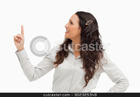 Brunette pointing up stock photo, Brunette pointing up against white background  by Wavebreak Media