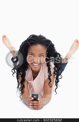 A smiling young woman is holding a mobile phone and smiling at t stock photo, A young smiling woman is lying on the floor holding a mobile phone against a white background by Wavebreak Media