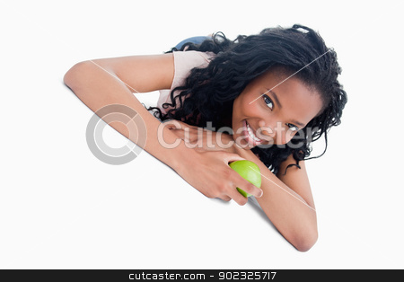 A young girl lying on the ground holding an apple stock photo, A young girl is lying on the floor holding a green apple against a white background by Wavebreak Media