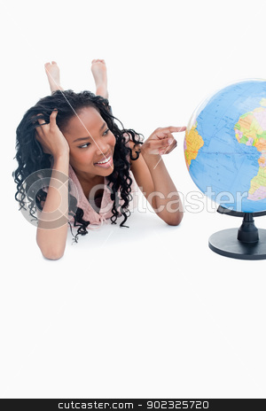 A young girl lying on the floor is pointing at a globe stock photo, A young smiling girl is lying on the floor pointing at a globe against a white background by Wavebreak Media