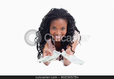 A smiling young woman is holding American dollars out in front o stock photo, A young smiling woman is holding American dollars out in front of her against a white background by Wavebreak Media