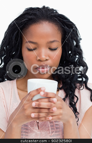A young woman with her eyes closed is smelling coffee out of a c stock photo, A young woman has her eyes closed and is smelling coffee out of a cup she is holding by Wavebreak Media