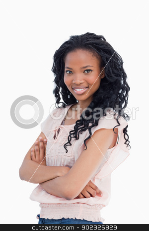 A young woman looking towards the camera with her arms folded stock photo, A young woman is looking towards the camera with her arms folded against a white background by Wavebreak Media