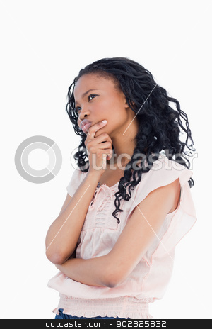 A young woman resting her head in her hand is thinking stock photo, A young woman is resting her head in her hand and is thinking against a white background by Wavebreak Media