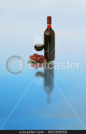 Wine bottle and a glass with grapes stock photo, A wine bottle and a glass with grapes by vaeenma