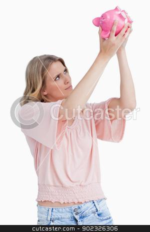 Woman looking inside of a piggy bank stock photo, A woman is looking inside of a pink piggy bank by Wavebreak Media