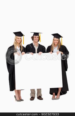 Three students in graduate robe holding a blank sign stock photo, Three students in graduate robe holding a blank sign against white background by Wavebreak Media