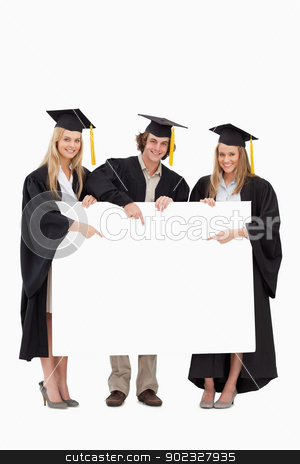 Three students in graduate robe holding and pointing a blank sig stock photo, Three students in graduate robe holding and pointing a blank sign against white background by Wavebreak Media