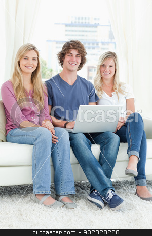 A group of friends sitting together as they use a laptop  stock photo, A smiling group of friends sit together while looking at the camera with a laptop in their hands  by Wavebreak Media