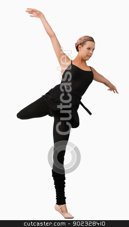 Female dancer standing on one foot stock photo, Female dancer standing on one foot against a white background by Wavebreak Media