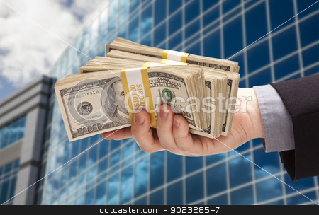 Male Hand Holding Stack of Cash with Corporate Building stock photo, Male Hand Holding Stack of Cash with Corporate Building Background. by Andy Dean