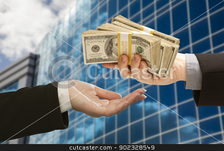 Male Handing Stack of Cash to Woman with Corporate Building stock photo, Male Hand Handing Stack of Cash to Woman with Corporate Building. by Andy Dean