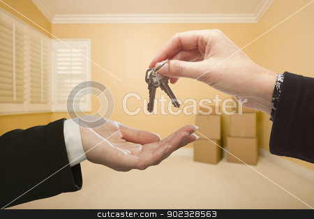 Woman Handing Over the House Keys Inside Empty Room stock photo, Woman Handing Over the House Keys To A New Home Inside Empty Room. by Andy Dean