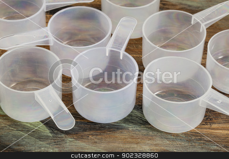 measuring scoops stock photo, empty plastic measuring scoop on painted wooden board - nutrition concept by Marek Uliasz