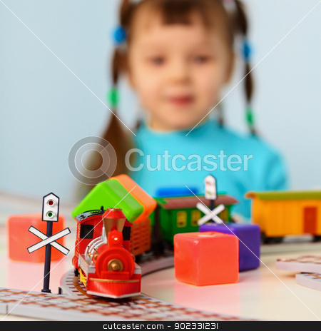 Little girl with toy railroad stock photo, Little girl plays with a toy railroad by Alexey Romanov