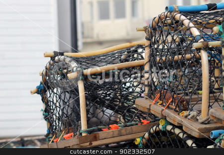 Lobster pots and creels stock photo, Lobster pots and creels with building in background and copy space. by Martin Crowdy