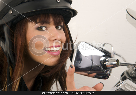 Beautiful Brunette Biker Holding the Handlebars stock photo, Beautiful Brunette preps for her ride checking her look in the mirror by Christopher Boswell