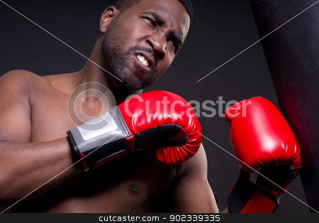Boxer on Blcak With Red Gloves stock photo, A boxer punches a heavy bag by Christopher Boswell