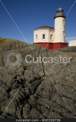 Rocky Lighthouse on the Pacific Ocean stock photo, West Coast Lighthouse on a rocky jetty by Christopher Boswell