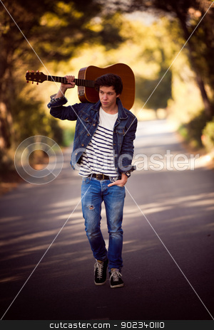 man with guitar stock photo, drifter, man with guitar walking outdoors by mandygodbehear