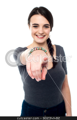 Cheerful young girl pointing you out stock photo, Pretty young smiling teenager pointing towards you. by Ishay Botbol