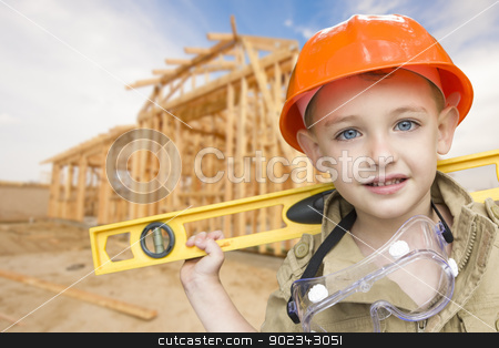 Child Boy Dressed Up as Handyman in Front of House Framing stock photo, Child Boy Dressed Up as Handyman in Front of New House Framing. by Andy Dean