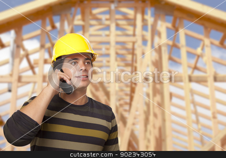 Hispanic Male Contractor on Phone in Front of House Framing stock photo, Handsome Hispanic Male Contractor on Phone in Front of New House Framing. by Andy Dean