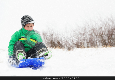 A young boy shows his excitement sledding down a hill in winter stock photo, A young boy shows his excitement sledding down a hill in winter by Artush