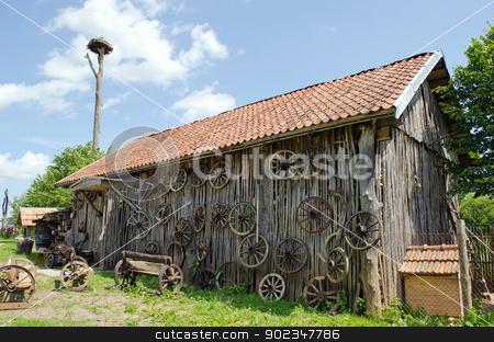 retro carriage wheel barn house bench stork nest  stock photo, retro carriage wheel hang on rural barn house. wooden benches. stork nest on top.  by sauletas