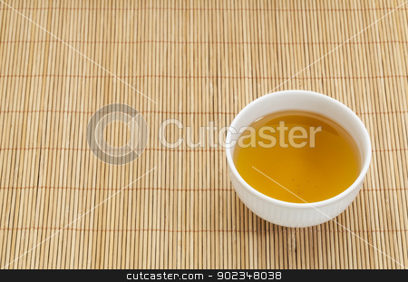green tea cup stock photo, white china cup of green tea against bamboo place mat by Marek Uliasz
