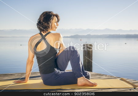 yoga woman stock photo, An image of a pretty woman doing yoga at the lake - Ardha Matsyendrasana  by Markus Gann