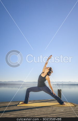 yoga woman stock photo, An image of a pretty woman doing yoga at the lake - Parivrtta Parshvakonasana  by Markus Gann