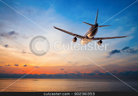 Airplane flying at sunset  stock photo, Airplane flying above tropical sea at sunset  by Iryna Rasko