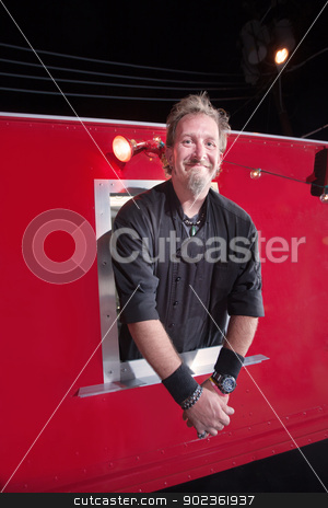 Smiling Chef at Canteen stock photo, Smiling handsome chef sticking out of restaurant truck by Scott Griessel
